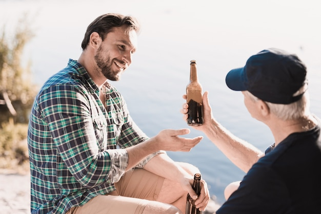 Smiling men drinking beer near river in summer. Premium Photo