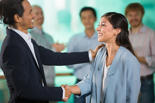 Smiling middle-aged business people shaking hands Free Photo