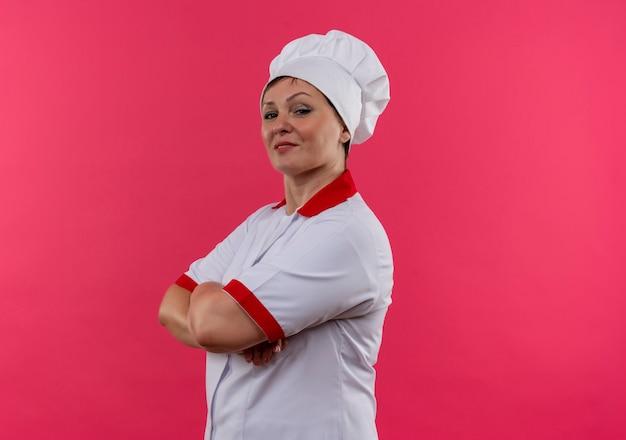 Cuoco femminile di mezza età sorridente nelle mani dell'incrocio dell'uniforme del cuoco unico con lo spazio della copia Foto Gratuite