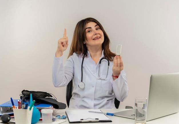 Улыбающаяся женщина-врач средних лет в медицинском халате со стетоскопом, сидя за столом, работает на ноутбуке с медицинскими инструментами, держит лампочку и указывает на белую стену Бесплатные Фотографии