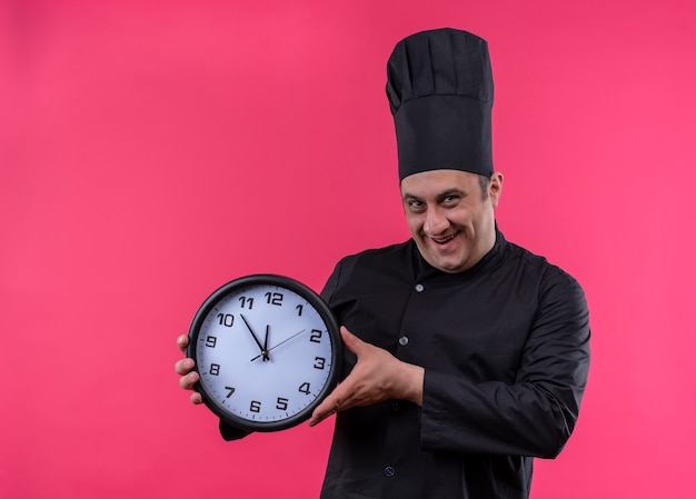 Cuoco maschio di mezza età sorridente in orologio da parete della tenuta dell'uniforme del cuoco unico con lo spazio della copia Foto Gratuite