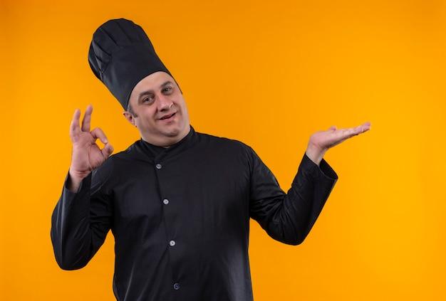 Cuoco maschio di mezza età sorridente in uniforme del cuoco unico che mostra okey su fondo giallo con lo spazio della copia Foto Gratuite