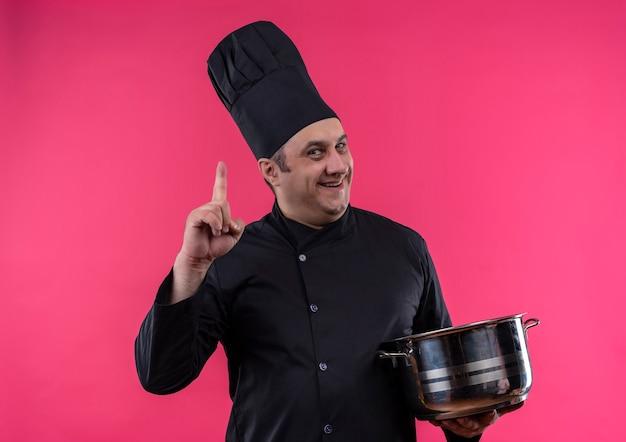 鍋を持ったシェフの制服を着た笑顔の中年男性料理人がコピースペースで指を上に向ける 無料写真