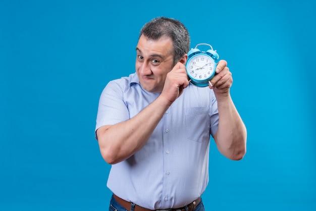 青い背景に青い目覚まし時計を保持している時計のカチカチという音を聞いて青い縦縞のシャツを着ている中年の男の笑顔 無料写真