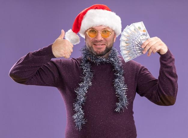 보라색 벽에 고립 된 엄지 손가락을 보여주는 돈을 들고 안경 목에 산타 모자와 반짝이 갈 랜드를 입고 웃는 중년 남자 무료 사진