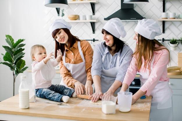 生地を伸ばしてキッチンエプロンで笑顔の中間老婆と彼女を助ける2人の娘。テーブルの上に座って楽しんでlitle女の赤ちゃん。一緒に焼く白いエプロンで幸せな女性 Premium写真