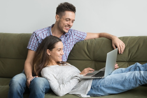 Smiling millennial couple enjoying using laptop relaxing on couch together Free Photo