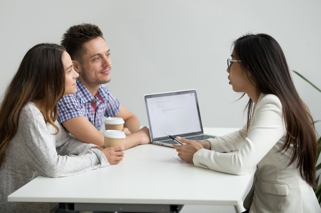 Smiling millennial couple listening to asian advisor lawyer consulting customers Free Photo