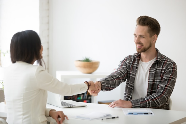 Handshaking sorridente dei soci millenari in ufficio che ringrazia per il riuscito lavoro di squadra Foto Gratuite