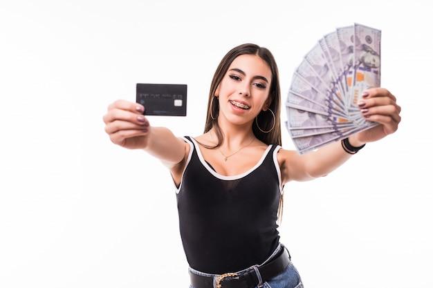 黒いシャツで笑顔のモデルは、ドル札とクレジットカードのファンを保持します。 無料写真