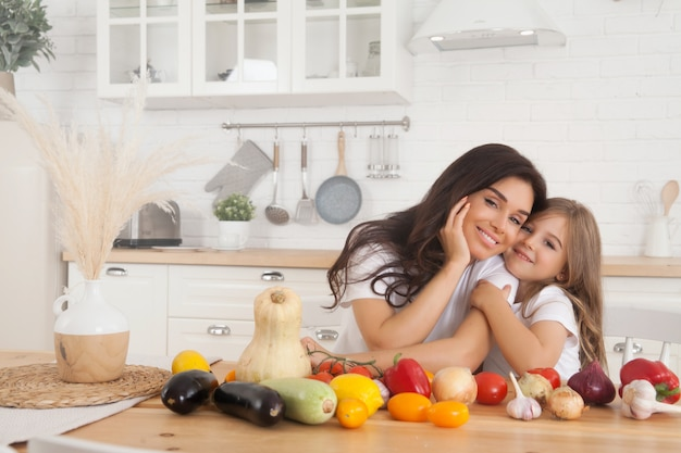 Smiling mom and daughter cooking fruits and vegetables in the scandinavian-style kitchen. Premium Photo