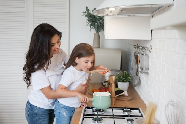 Smiling mom and daughter cooking in the scandinavian-style kitchen on white Premium Photo