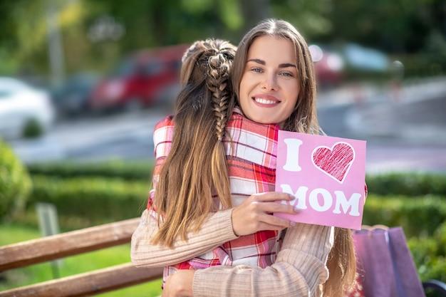 인사말 카드를 들고 그녀의 딸을 껴 안은 웃는 엄마 프리미엄 사진
