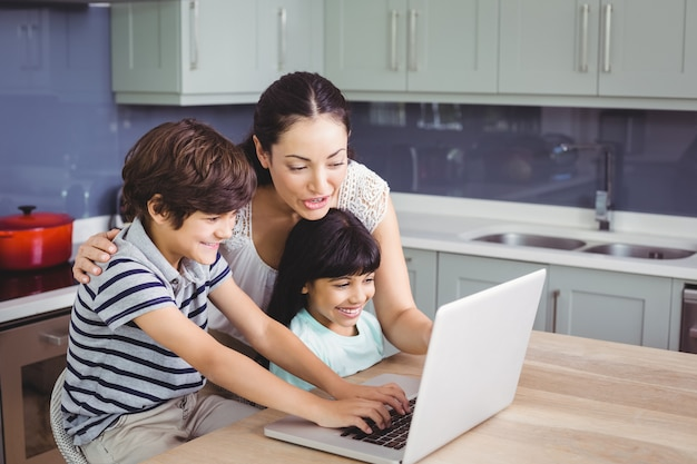 Smiling mother and children working on laptop Premium Photo
