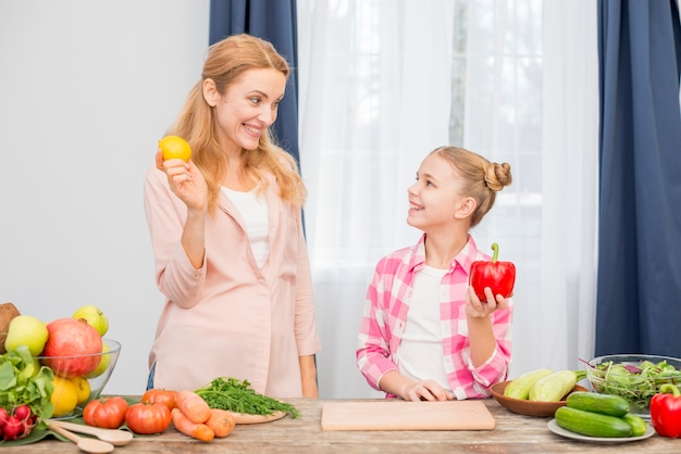 Smiling mother and daughter holding yellow lemon and red bell pepper in hand Free Photo