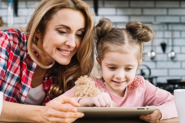 Smiling mother and daughter using digital tablet in kitchen Free Photo