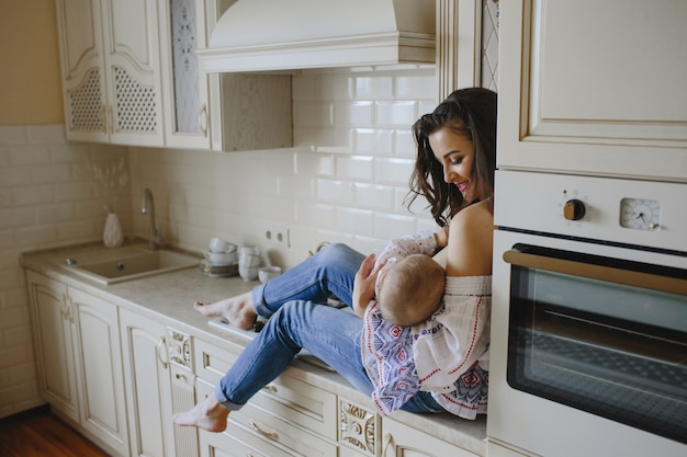 A smiling mother holds the baby in her kitchen Free Photo