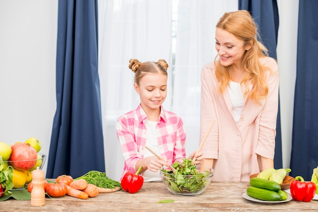 Smiling mother looking at her daughter preparing salad in the glass bowl on wooden table Free Photo