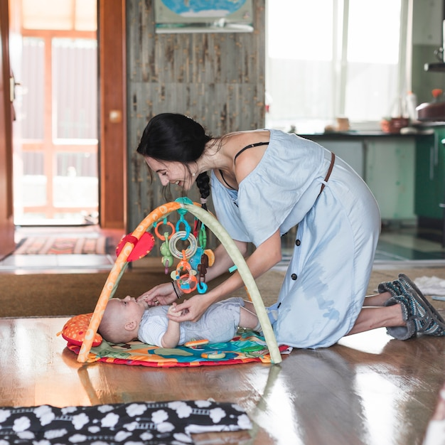 Smiling mother playing with her baby lying on developing rug with mobile educational toys Free Photo