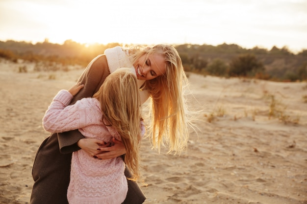 Smiling mother playing with her little daughter Free Photo