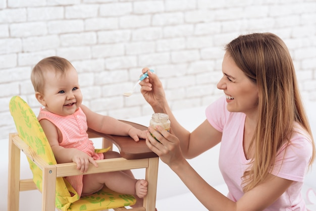 Smiling mother with puree feeding smiling baby Premium Photo