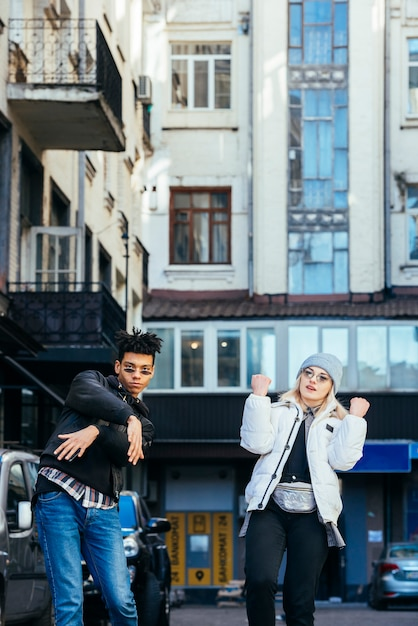 Smiling multi ethnic young couple standing under the building dancing on street Free Photo