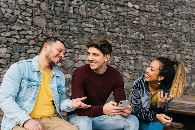 Smiling multiethnic friends talking and looking at phone Free Photo