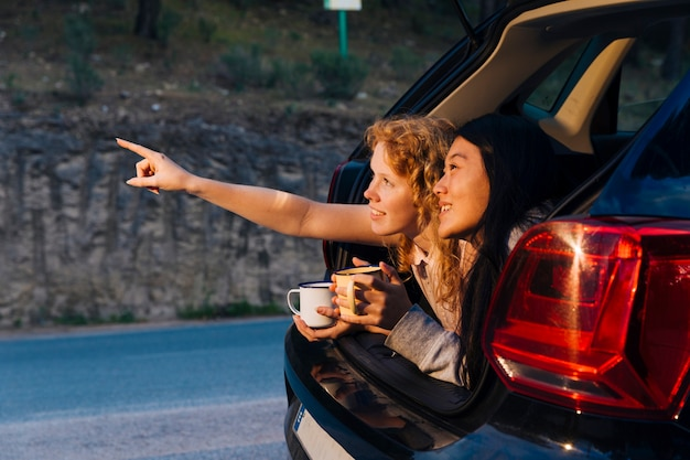 Smiling multiethnic girlfriends relaxing in trunk Free Photo