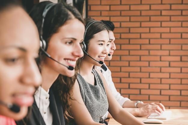 Smiling multiethnic telemarketing customer service agent team working in call center office Premium Photo