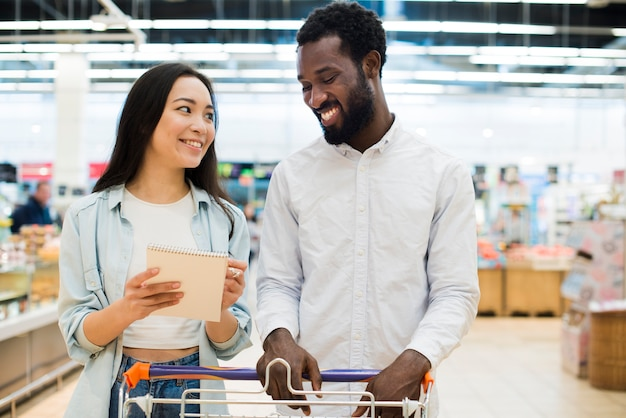 Smiling multiethnical couple buying goods in supermarket Free Photo