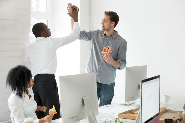 Smiling multiracial coworkers giving high-five eating pizza together at office Free Photo