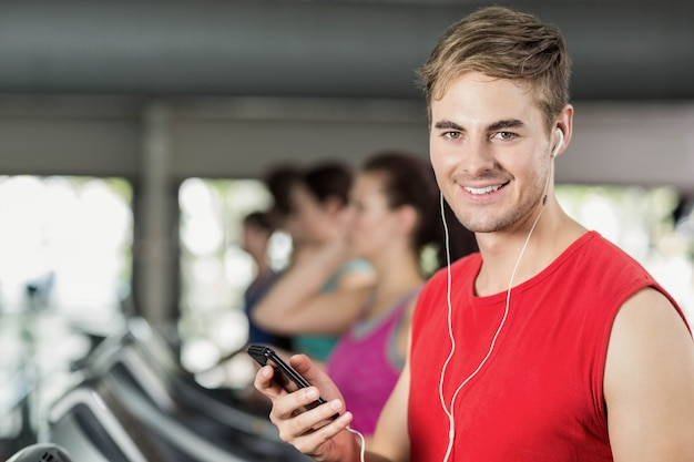 Smiling muscular man on treadmill listening to music at gym Premium Photo