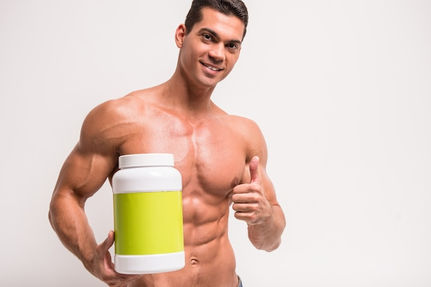 Smiling muscular man with jar of protein. Premium Photo