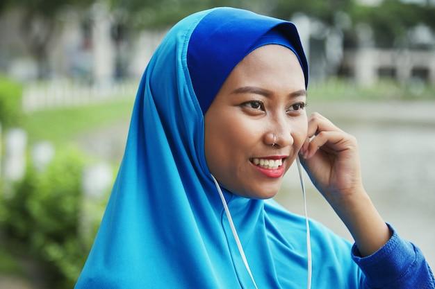 Smiling muslim woman plugging earphones on street Free Photo