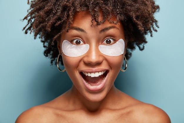 La donna nuda sorridente ha una pelle sana, cerotti cosmetici sotto gli occhi, gode di trattamenti di bellezza o per gli occhi, rimuove le rughe, ha un ampio sorriso, denti bianchi perfetti, ha le spalle nude. trucco naturale Foto Gratuite