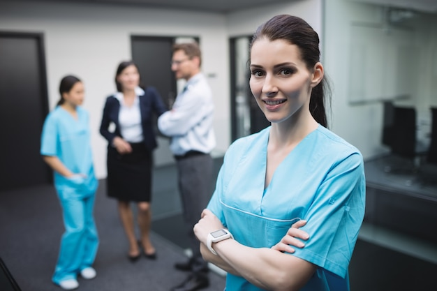 Smiling nurse standing with arms crossed Free Photo