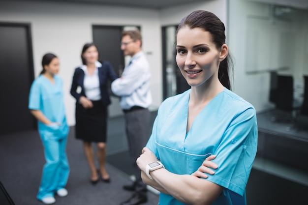 Улыбающаяся медсестра, стоя со скрещенными руками Бесплатные Фотографии