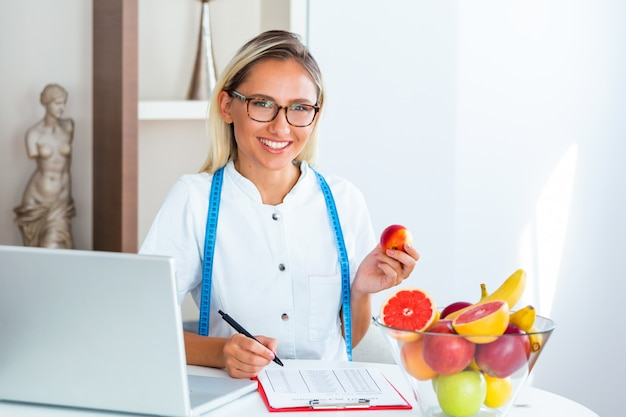 Smiling nutritionist in office holding a fruit Premium Photo