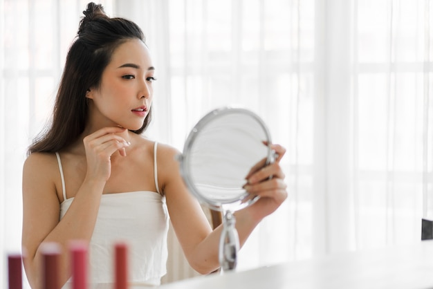 젊은 아름 다운 아시아 여자 깨끗 하 고 신선한 건강 한 하얀 피부 미소 거울. 소녀 손으로 그녀의 얼굴을 만지고 집에서 크림을 적용. 스파 및 뷰티 개념 프리미엄 사진