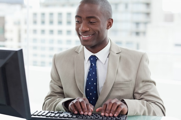 Smiling office worker using a computer Premium Photo