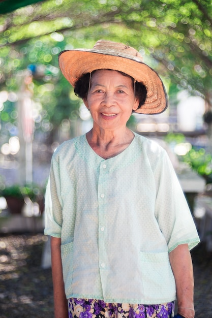 Smiling old asian farmer woman standing with happy. Premium Photo