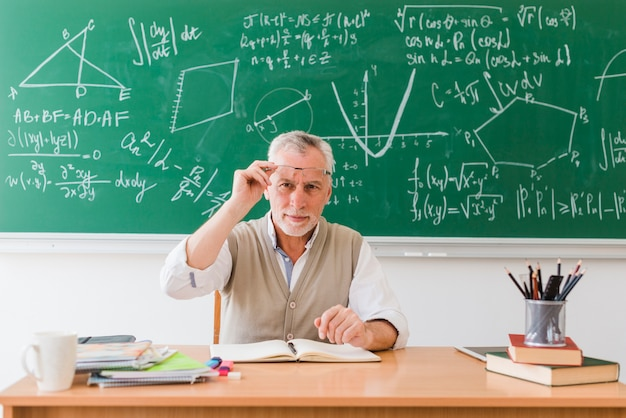 Smiling old professor of maths in classroom Free Photo