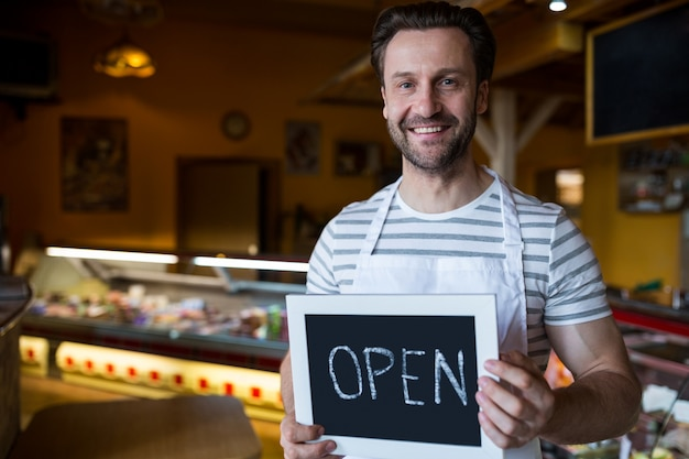 Smiling owner holding a open sign in the bakery shop Free Photo