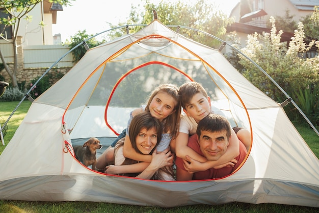 Smiling parent enjoying holiday picnic with their children in tent Free Photo