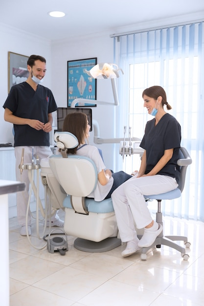 Smiling patient and dentist's in dental clinic Free Photo
