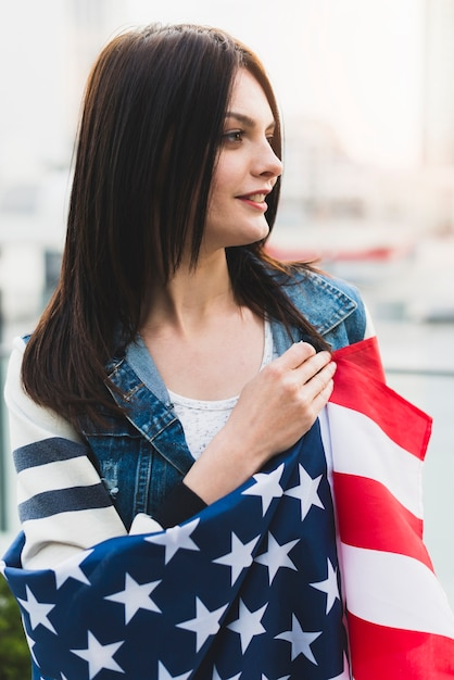 Smiling patriotic woman wrapped in usa flag Free Photo