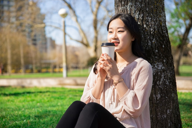 Smiling peaceful girl drinking takeaway coffee in city park Free Photo