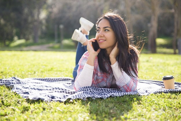 Smiling pensive girl resting on grass and speaking on cell Free Photo