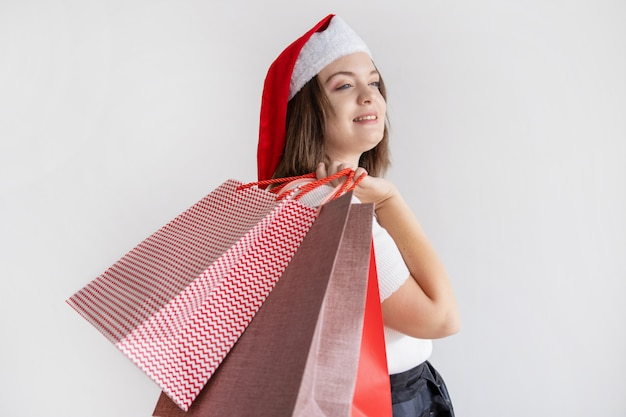 Smiling pensive lady holding shopping bags on shoulder Free Photo