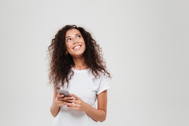 Smartphone pensieroso sorridente della tenuta della donna in mani e cercare sopra il fondo grigio Foto Gratuite
